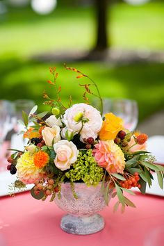 What a color palette! Sunny shades of flowers and berries grace the coral tables. Dia Rao Photography.