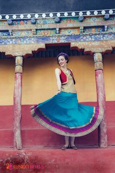 Go traditional with this blue skirt, golden top and red jacket.