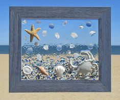 "Unique beach window art by Luminosities! Hand painted, cast iron crab in a sea of shells, starfish, sand dollars, sea glass and blue frosted gems. Set in a blue, wooden frame.  Measurements are 10.5""x12.5"""