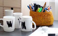 Superficie de trabajo con tazas con dibujos hechos a mano y un cesto con bolígrafos y una libreta