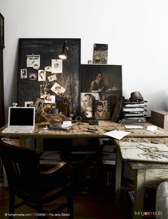 Rustic office area with studio character; laptop on wooden table, photographs stuck on blackboard and various paintings leaning against wall | © living4media | Pia Jane Bijkerk | 11338301