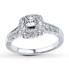 A princess-cut diamond is the highlight of this amazing engagement ring for her. Two rows of round diamonds frame the center, with more round diamonds set into the band of 14K white gold. Milgrain detailing gives this ring a simple vintage allure. The ring has a total diamond weight of 3/4 carat. Diamond Total Carat Weight may range from .69 - .82 carats.