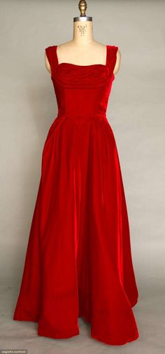 CEIL CHAPMAN RED BALLGOWN, 1948-1952 Labeled, garnet red velvet, wide shoulder straps, fitted bodice w/ front & back piped V points, fabric softly ruched over breasts, full length circle skirt, heavy stiffened facing in skirt. Front