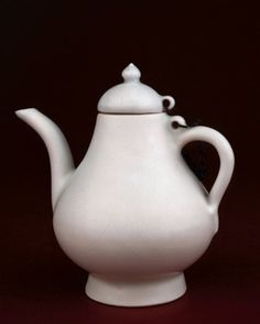 White porcelain wine pot. Covered with grey-toned glaze. Finat incised design, with cloud collar on the cover, classic scroll on the spout and lotus scroll on the body. A chain attaches the cover to the pot. (Ming dynasty)