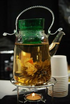 Glass tea pots with blooming Tea & champagne with buds. Take home hand selected tea mix favor.