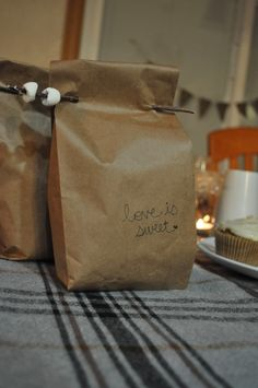 "FAVORS: caramel apples wrapped in kraft paper bags, hand-lettered with ""love is sweet"" and enclosed with mini marshmallow roasting twigs for guests to take home. [field notes]"