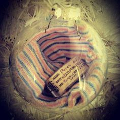Baby's hat and hospital bracelet inside a clear Christmas ornament.