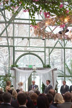 *Snow falls outside as they wed inside a glass chapel...