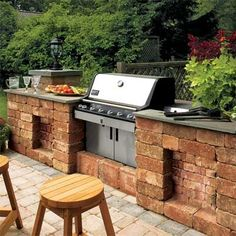 "Here, a peninsula of tumbled cast-concrete blocks and a stone counter turns a freestanding grill into a built-in. DIY this setup for about $350 by stacking blocks on a bed of tamped drainage stone, securing each block with masonry glue. Incorporate blocks of varying sizes and recessed ""panels"" to make the unit look less monolithic, then top it off with bluestone stair treads for the counter."