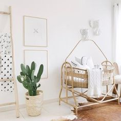 A rattan bassinet looks so good in a white nursery with just a few green plants ! Nursery styled by in collaboration with and Want to be featured on our feed ? Use for your nursery or kid's room pics !