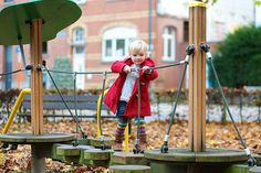 Jesień, dziewczynka na placu zabaw wspina się po drabinkach