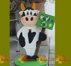 stehende Kuh aus Holz mit Holzschild