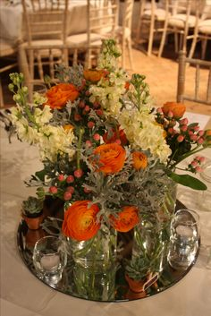 Table Centre made up of 3 Jam Jars containing Ranunculus, Stocks, Hypercium Berries and Senecio.  Surrounded by candles and small potted succulents. #Table #Centre #Reception #Wedding