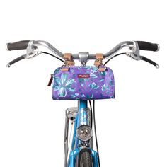 Six Corners Handlebar Bag converts to a crossbody bag off the bike. Made with weatherproof, vegan fabric. Shown in purple Petals color.