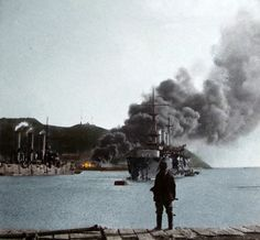 A man watches stranded Russian ships and an oil depot fire started by Japanese shelling in the besieged city of Port Arthur, 1904
