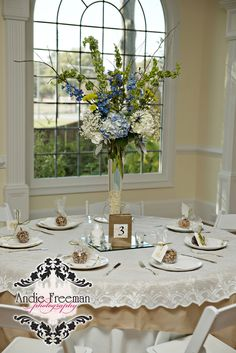 Reception tablescapes with burlap and lace table cloths.  Tall centerpieces with blue and white hydrangeas.   Burlap covered vintage books for table numbers. Classic Shabby Chic Fall Wedding. Photography: Andie Freeman Photography www.TheAthensWeddingPhotographer.com Wedding Planning and Coordinating: www.WildflowerEventServices.com Venue and Floral: The Thompson House and Gardens