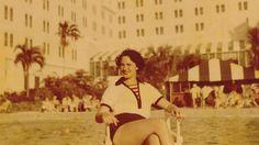 A woman sits outside a hotel pool.