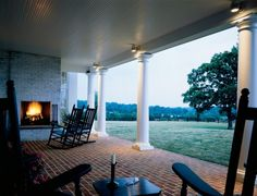 traditional patio/covered porch...brick floor, wooden ceiling, columns, and fireplace with rocking chairs
