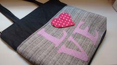 Bolsa de tecido jeans escuro, forrada com zíper, bolso interno também com zíper e bolso externo com manta e quilt e fecha com botao imantado