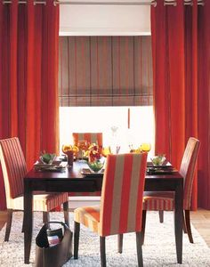 Red drapery panels and striped Roman shade for a striking layered look in this dining room.