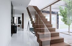Made from the same dark hardwood that features in the kitchen, this staircase with glass side panels is modern minimalism at it's very best. Simple and elegant. Design by HomeKONCEPT Beautiful House Plans, Beautiful Homes, Modern Family, Home And Family, House Entrance, Design Case, Home Projects, My House, Building A House