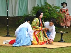 A woman (with attendants) playing the empress (or some other high ranking station) at a Kyokusui No En ( a heian era poetry party)