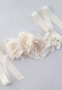 This is a gorgeous floral sash with three silk ivory roses with ivory velvet leaves , all attached onto ribbon of your colour and choice Normally