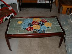 Coffee table on castors. Mosaic of a vase of flowers.~~Made by Diane Erickson~~   Sold