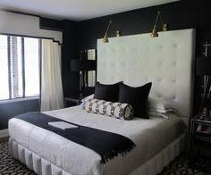 chambre noble avec tête de lit blanche et capitonnée et deux appliques liseuse en laiton