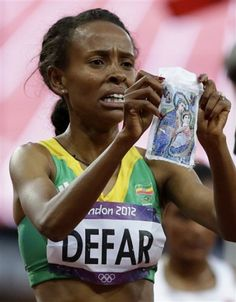 Ethiopian Christian Meseret Defar won the women's 5,000 meter Gold Medal on Friday then she knelt and wept on the track while clutching a picture of Jesus and Mary