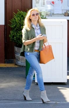 Reese Witherspoon wears a plaid button-down shirt by Rails, army green jacket, belted skinny jeans, Rag & Bone gray boots, and a tan leather tote bag