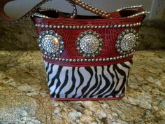 Raviani Handbag (Made In USA)    Red croco leather with zebra hair on leather with three beautiful conchos,    this bag has silver nailheads, magnetic snap closure, inside pockets and nailhead all over the strap.  bag size 11''H x10''W x5''D