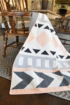 """This throw size quilt is the perfect addition to your living room! It features modern geometric shapes that all come together to form a cohesive picture that is inspired by the Native American culture in Western North Carolina. It measures about 50"""" x 65"""", and is made with 100%"""