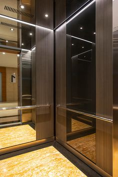 LEVELe-105 Elevator Interior with customized panel layout; Minimal panels in Bonded Aluminum with Dark Patina and Loft pattern, Mirror glass, and ViviChrome Chromis glass with Black interlayer and Standard finish; base panel in Stainless Steel with Seastone finish; Round handrails with radius bend ends in Polished Stainless Steel; ceiling in Stainless Steel with Mirror finish; LED downlights and perimeter accent lighting at 1 Sobha Mall, Bengaluru, India Cabin Interior Design, Cabin Design, Elevator Lobby Design, Stair Lift, Lift Design, Tiny Apartments, Commercial Interiors, Home Decor Furniture, Building Design