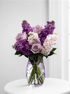 Purple flowers and pink flowers arranged in a purple vase including purple roses
