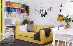 Ein Wohnzimmer in Weiß, dekoriert mit Akzentfarben an den Wänden und am Esstisch.