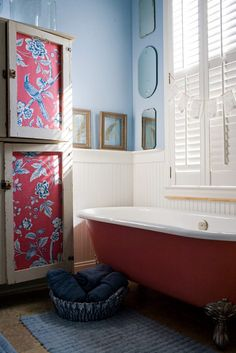 Corbin Lee Gurkin Bathroom: Raspberry red clawfoot tub, Farm cabinet with patterned fabric panels on doors.