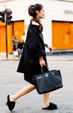 Peony Lim wears an off-the-shoulder black dress, furry slide sandals, and an Hermes Birkin bag