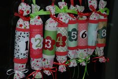 My homemade advent calendar for 2011 - TP tubes covered in crepe paper, decorative scrapbook paper and a small punch with a chipboard sticker number.  Inspired by Christmas crackers, the little bags are made of fabric with ribbon sewn in to tie each end shut and a little loop at the top to hang them by.