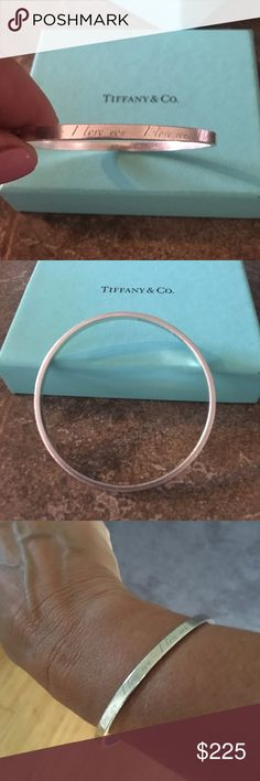 "TIffany and Co I LOVE YOU notes silver bracelet. Authentic Tiffany sterling silver bracelet says I love you over and over it. It's from the ""notes"" collection. It is genuine .925 sterling silver. There is one nick in the side of it as shown in the photo. It is preowned , pre worn and pre loved. It is not new. It is rare as it is no longer available from Tiffanys. It comes with the Tiffany box however the box is stained on the inside so would not be good for gift giving. Make me an offer and…"
