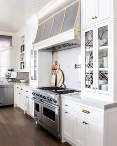 Dream kitchen is an understatement for this classic white space. Designed with quartzite and brass details, larger than life pendants, two islands and cabinets with wallpapered interiors, it takes luxury to a whole new level. Gray And White Kitchen, Gold Kitchen, New Kitchen, White Wood, Kitchen Ideas, Kitchen Decor, Kitchen Hoods, Kitchen Cabinets, Kitchen Hood Design
