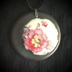Translucent porcelain pendant. Metal saturate glaze, vintage floral transfer. Sterling silver bail, wrapped silk cord, adjustable...choker to necklace lengths.