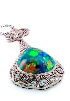 "Very Rare Art Deco Black Opal and Diamond Necklace, Circa 1925, featuring a spectacular teardrop-shaped, high domed, black opal weighing approximately 6.50 to 7carats, bezel-set on a milegrained and pierced platinum frame set with diamonds, suspended from a platinum and 14 karat white gold, 17 1/2"" long diamond chain. Forty-seven diamonds in all totaling approximately 1.50 carats, the pendant portion approximately 1 1/2"" long and 3/4"" wide."