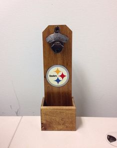 My Pittsburgh Steelers wall mounted bottle opener is custom made from durable poplar wood. It is stained and also has two coats of polyurethane. It contains a bottle cap catcher that is built in. There are no exposed nails to be seen in this bottle opener. All mounting hardware is included. Can be custom made to cater to all size preferences.  Dimensions: 12Hx 4W x 3D