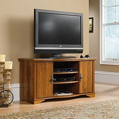 Accommodates up to a 46 in. TV weighing 95 lbs. or less.    The storage area behind doors in this entertainment credenza has an adjustable shelf and holds 108 CDs or 84 DVDs.  Two adjustable shelves hold audio/video equipment.  Accented with solid wood detailing.  Abbey Oak finish.