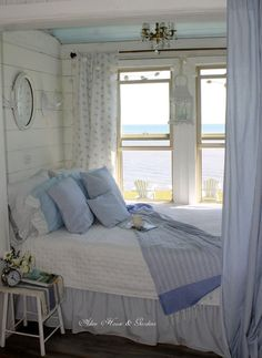 Pretty blue and white small space bedroom under a window