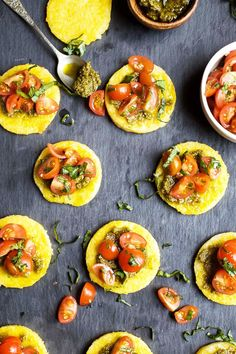 PESTO POLENTA BITES WITH TOMATO BRUSCHETTA. 17 Small Bites for Your Next Summer Soirée #purewow #cooking #food #recipe #entertaining #summer #party #appetizer #smallbites #easyappetizers #fingerfoods #apps #summerparties #partyfood #summerrecipes #polenta #pesto