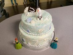 Two tier Frozen themed cake. Olaf and the  toboggan are sculpted from modeling chocolate. The snow flakes are white chocolates brushed with shimmer dust. Snowballs are pearl chocolate candies.