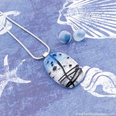 Handmade Liquid Ocean glass pendant, glistening silver with a glacial blue and jet black design.Together with the handmade glass Ocean Earrings.