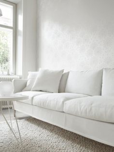 Beautiful all white minimalist living room interior with tone on tone wallpaper.
